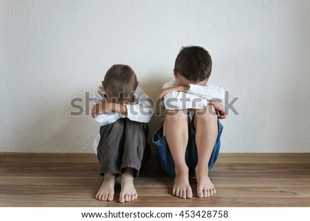 sad boys sitting in the room with his head down - stock photo