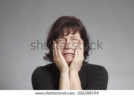 Sad brunette woman against gray background