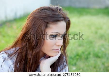 Sad brunette woman in park thinking something - stock photo