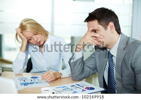 Sad business partners at workplace, focus is on confused male - stock photo