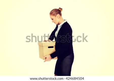 Sad business woman carrying box after loosing job - stock photo