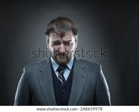 Sad businessman agaist gray - stock photo