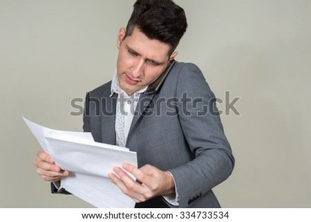 Sad businessman looking papers and using mobile phone