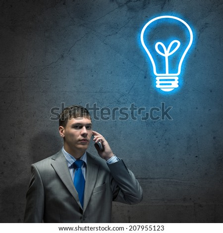 sad businessman talking on a cell phone with tears in his eyes
