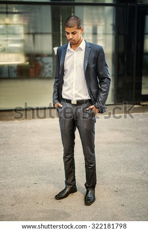 Sad businessman, victim of racism, standing in front of his office and looking down. He is unlucky, depressed, unemployed. - stock photo