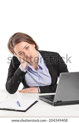 Sad businesswoman sitting at a table isolated on white background - stock photo