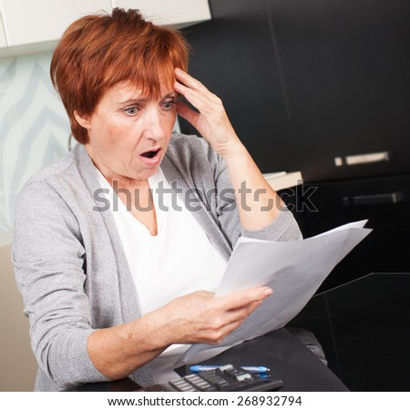 Sad businesswoman with document. Elderly woman sorting through her old receipts at home.  - stock photo