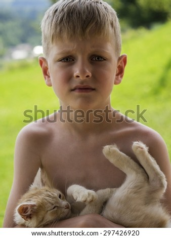 Sad caucasian boy with red kitten, outdoor - stock photo