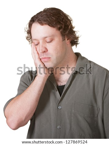 Sad Caucasian male with hand on cheek looking down - stock photo