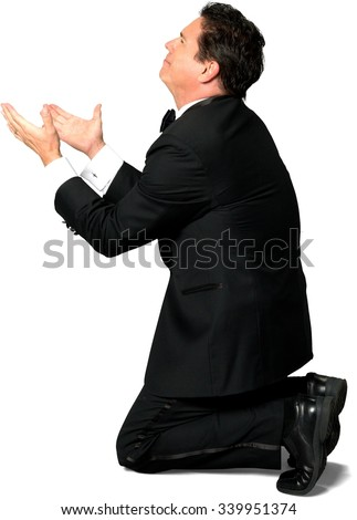Sad Caucasian man with short black hair in a tuxedo begging - Isolated - stock photo