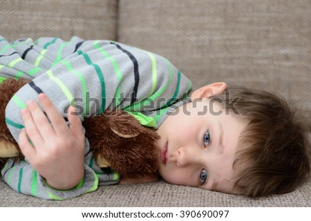 Sad child hugs his favorite teddy bear and lying on the sofa in the living room