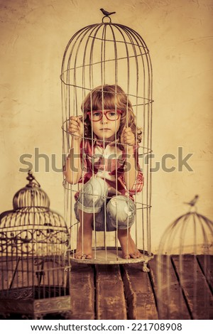 Sad child in steel cage. Human rights concept - stock photo
