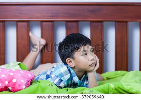 Sad child inside bedroom. Handsome asian boy lying on his bed looking sad and lonely. Problem families concept. - stock photo