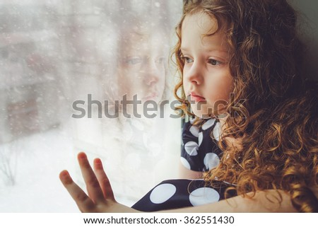 Sad child looking out the window on falling snow. Toning photo instagram filter. - stock photo