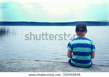 sad child sitting alone at the lake on a cloudy day, back view - stock photo
