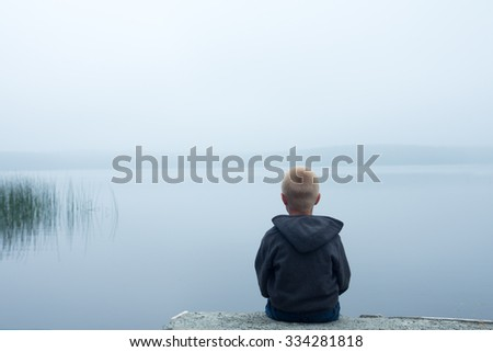 sad child sitting alone by lake in a foggy day, back view - stock photo