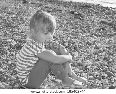 Sad child sitting on stones - stock photo