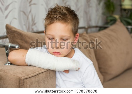 Sad child with a broken arm in the home environment . The cast on the hand of a little boy. Injury to a child is bored at home.  - stock photo