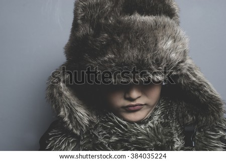 Sad child with fur hat and winter coat, cold concept and storm - stock photo