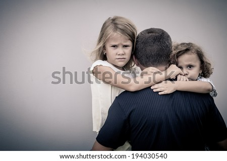 sad children hugging his dad - stock photo