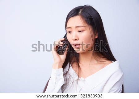 sad Chinese woman talking on a phone