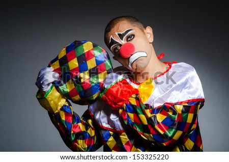 Sad clown against dark background - stock photo