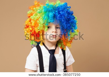 Sad clown. Little boy in clown wig smiling and having fun. Thoughtful clown boy with large colorful wig. Birthday boy. Little clown boy with colorful hair. Positive emotions.  - stock photo