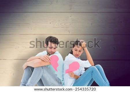 Sad couple sitting holding two halves of broken heart against shadow on wooden boards - stock photo
