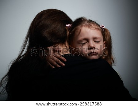 Sad crying daughter hugging her mother with sad face on dark shadows background - stock photo