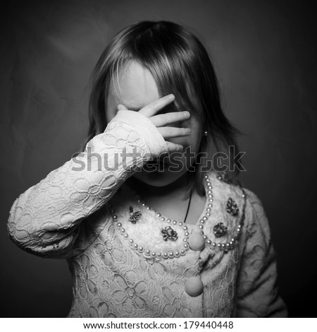 Sad crying little girl covers his face with hand - stock photo
