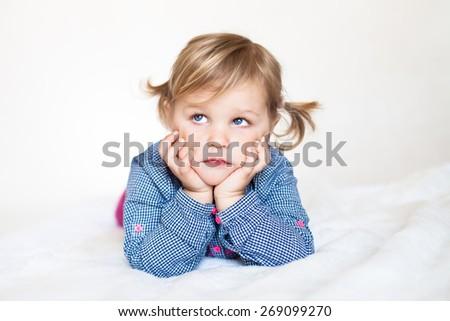 Sad cute baby girl lying on the white blanket - stock photo