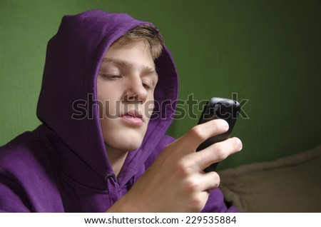 Sad depressed kid waiting for text message reply - stock photo