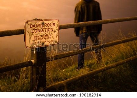 Sad/depressed man standing on edge of cliff behind a danger sign - stock photo