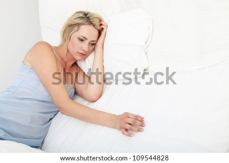 sad depressed woman propped up on pillows Sick depressed woman lying propped up on her pillows in bed in her nightgown - stock photo