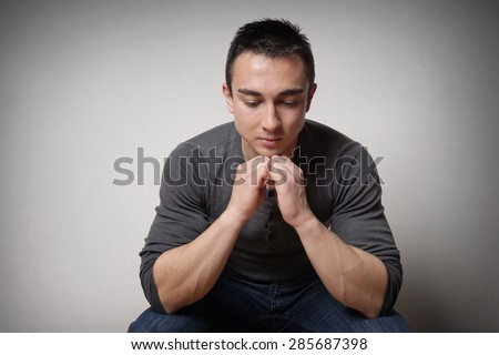 sad depressed young man lost in thought and looking down - stock photo