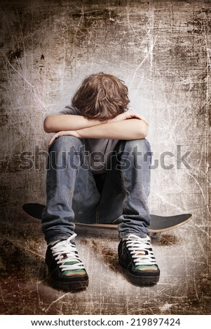 sad depression  teenager sitting on skateboard - stock photo