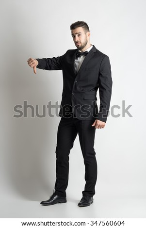 Sad displeased groom in suit with bow tie showing dislike thumbs down hand sign. Full body length portrait over grey studio background.