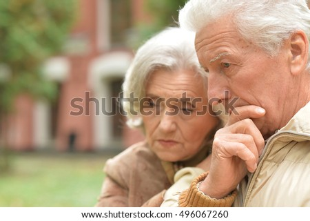 Sad elderly couple standing embracing outdoors