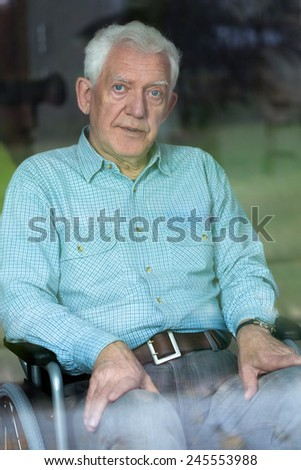 Sad elderly sick man sitting on the wheelchair
