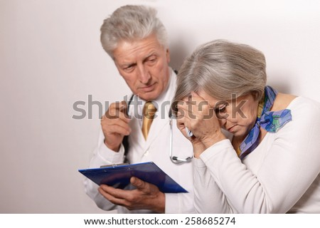 Sad  elderly woman came to the doctor - stock photo