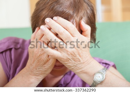 Sad elderly woman covering her face with her hands. - stock photo