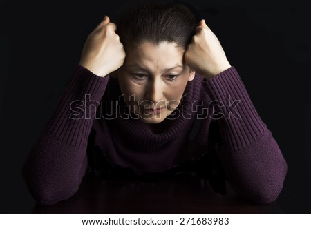 Sad elderly woman on a black background