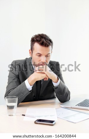 Sad employee sitting at the dest - stock photo