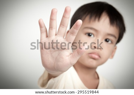 sad face of asian kid and hand raise to stop or protect  - stock photo
