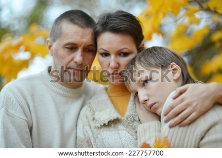 sad family of three on the nature - stock photo