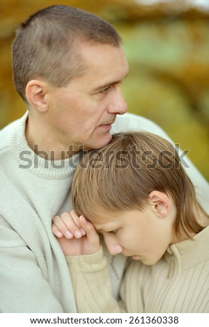 Sad father and boy in autumn park - stock photo