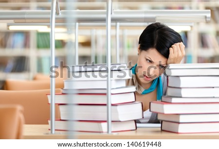 Sad female student is tired of training surrounded with piles of books sitting at the desk - stock photo