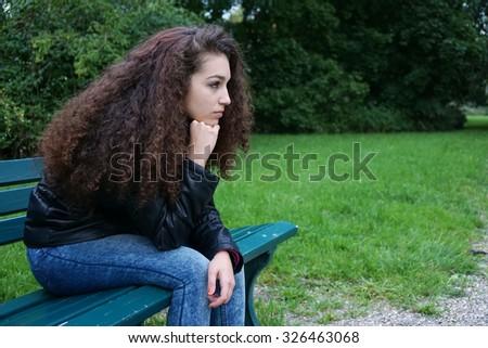 sad female teenager sitting on park bench - stock photo