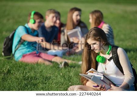 Sad female teenager sitting outdoors with books - stock photo