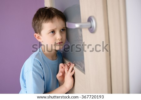 Sad, frightened child listening to a parent talking through the door with a glass pressed to his ear.